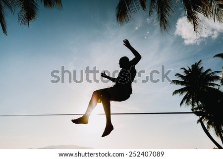 teenage  jumping and balancing on slackline silhouette and sunflare - stock photo
