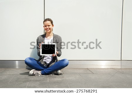 teenage laughing while look at Ipad by the glass wall - stock photo