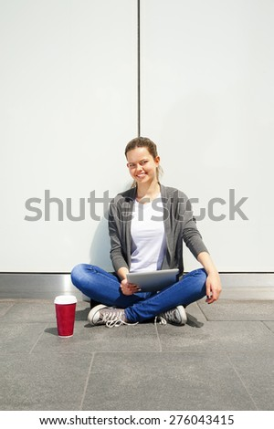teenage laughing while look at tablet by the glass wall with cafe cup - stock photo