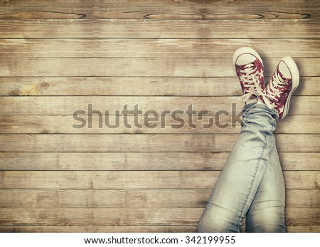 Teenage legs in sport shoes sitting on wooden background - stock photo