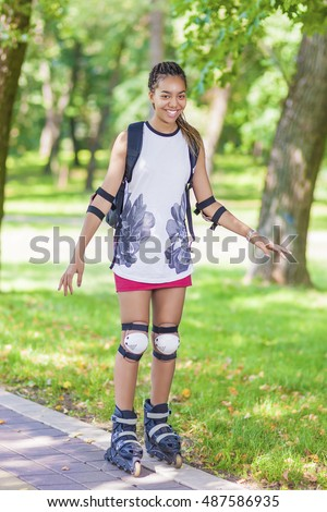 Teenage Lifestyle Concepts and Ideas. Sportive African American Female Teenager Having Fun on Roller Skates in Park. Vertical Image