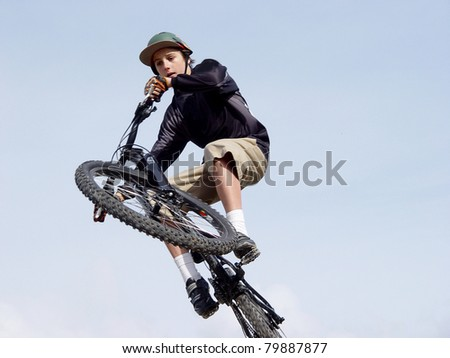 Teenage male doing high jump on a bmx bike, blue sky background - stock photo