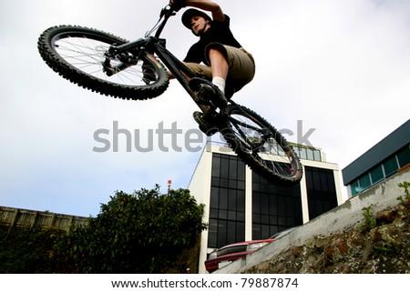 Teenage male doing high jump on a bmx bike off a ramp - stock photo