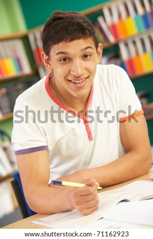 Teenage Male Student In Working In Classroom