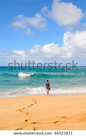 Teenage male walking into the surf on a tropical beach. Sunny day with bright blue sky and white fluffy clouds. - stock photo