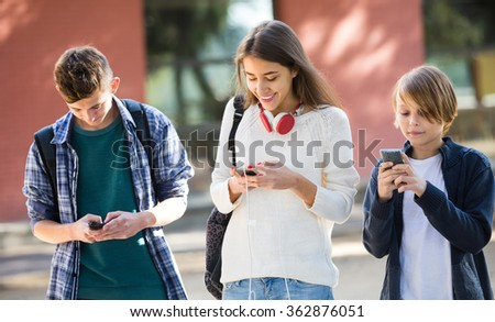 Teenage males and girl burying with mobile phones outdoor - stock photo