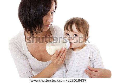 Teenage mother feeding her newborn baby with the bottle. Isolated on white. - stock photo