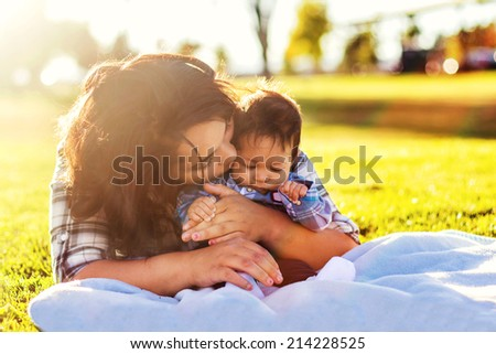 Teenage mother spending time with her 3 month old son at the park -- image taken at a park in Reno, Nevada - stock photo