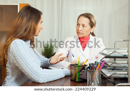 Teenage patient  and professional doctor at table in clinic - stock photo