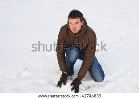 teenage playing snowball at winter day in brown jacket