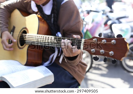 Teenage school girl playing an acoustic guitar with guitar song book - stock photo