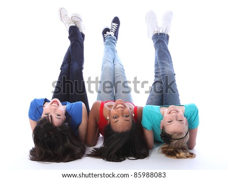 Teenage school student best friends lying on the floor looking backwards together made up of mixed race african american, oriental Japanese and caucasian all with happy smiles having a laugh. - stock photo