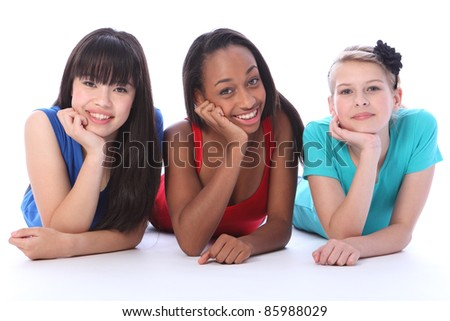 Teenage school student best friends lying on the floor together made up of mixed race african american, oriental Japanese and caucasian all with happy smiles having a laugh. - stock photo