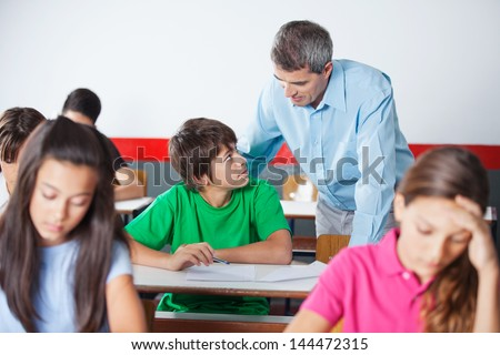 Teenage schoolboy and male teacher looking at each other during examination at desk in classroom - stock photo