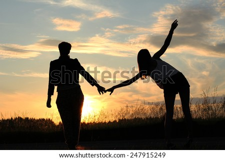 teenage sisters doing gymnastics outdoors, at sunset field - stock photo