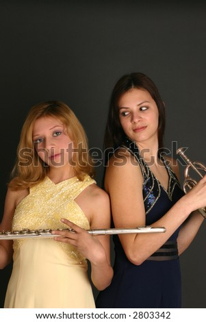 Teenage sisters with flute and trumpet and wearing prom dresses