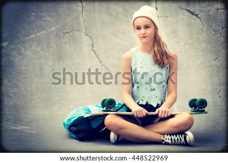 Teenage skater girl holding skateboard - stock photo