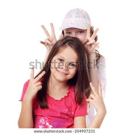 teenage smiling girls showing the victory sign - stock photo