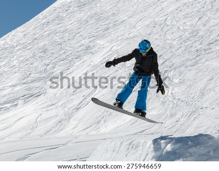 Teenage snowboarder in mid air after a jump on a snowboard.  The male is wearing a black jacket, blue trousers and helmet - stock photo