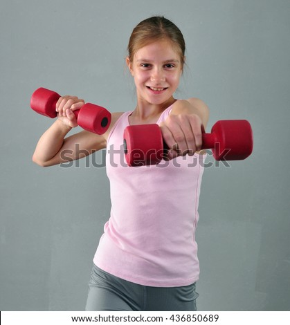 Teenage sportive girl is doing exercises with dumbbells to develop with dumbbells muscles on grey background. Sport healthy lifestyle concept. Sporty childhood. Teenager child exercising with weights. - stock photo