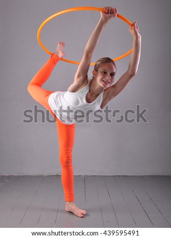 Teenage sportive girl is doing exercises with hula hoop on grey background. Having fun playing game hula-hoop. Sport healthy lifestyle concept. Teenager exercising with tool. - stock photo