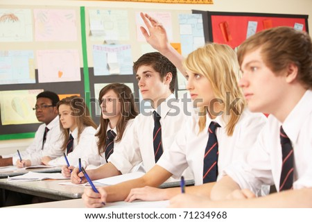 Teenage Student Answering Question Studying In Classroom - stock photo