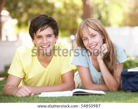 Teenage Student Couple Studying In Park - stock photo