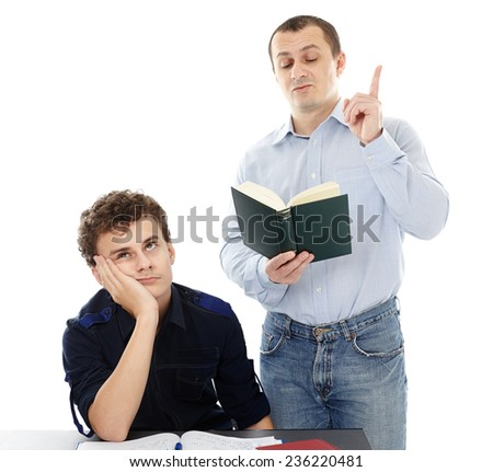 Teenage student displaying boredom sitting at his deks, while his father is lecturing - stock photo