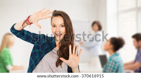 teenage student girl showing hands at school