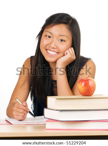 Teenage student girl smiling and sitting at desk stacked with books - stock photo