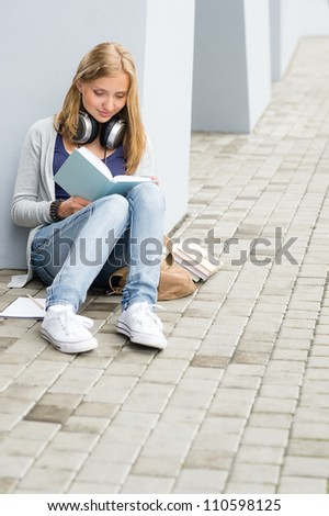 Teenage student girl study siting ground outside university building