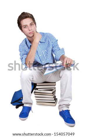 teenage student sitting on a stack of his textbooks on white background - stock photo