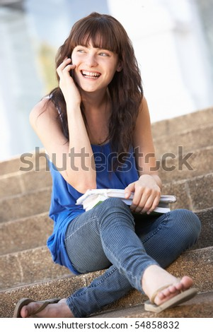 Teenage Student Sitting Outside On College Steps - stock photo
