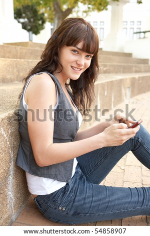 Teenage Student Sitting Outside On College Steps Using Mobile Phone - stock photo
