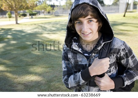 Teenage student (15 years) carrying book bag on shoulder, looking up smiling - stock photo