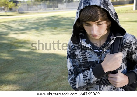 Teenage student (15 years) carrying bookbag on shoulder, looking down with serious expression - stock photo