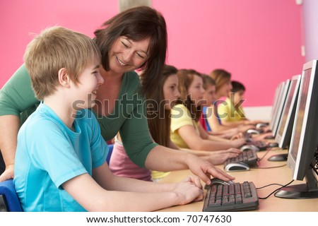 Teenage Students In IT Class Using Computers In Classroom With Tutor - stock photo