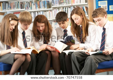 Teenage Students In Library Reading Books - stock photo