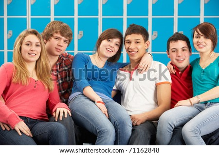 Teenage Students Relaxing By Lockers In School