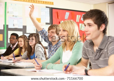Teenage Students Studying In Classroom Answering Question - stock photo