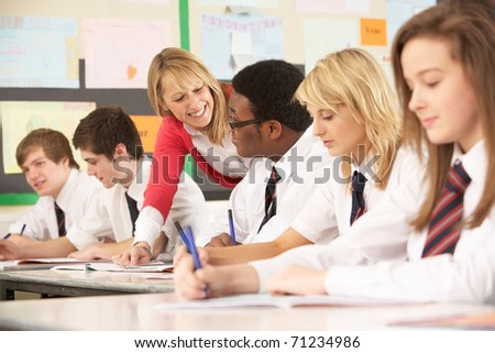 Teenage Students Studying In Classroom With Teacher - stock photo