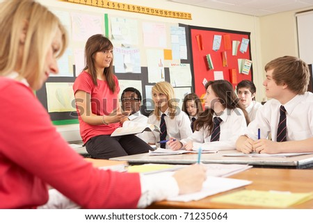 Teenage Students Studying In Classroom With Teacher And Assistant - stock photo
