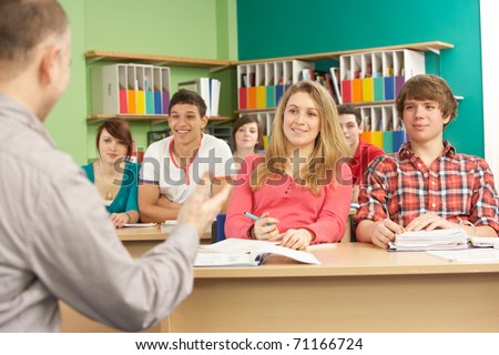 Teenage Students Studying In Classroom With Tutor - stock photo