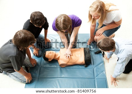 Teenage students use a mannequin to practice life saving techniques. - stock photo