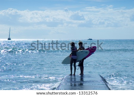 teenage surfers getting ready to get in the water - stock photo