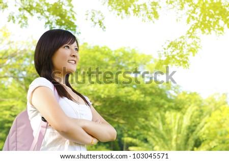 Teenage with school bag looking away in outdoor green park - stock photo