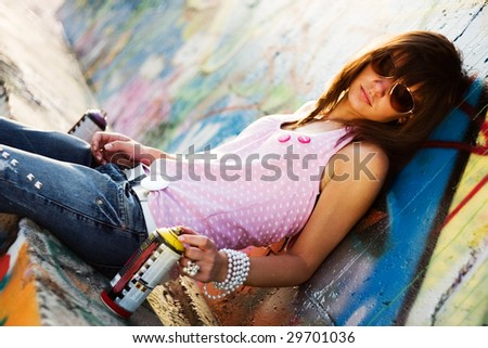 Teenage with sunglasses, with a graffiti background, fashion look - stock photo