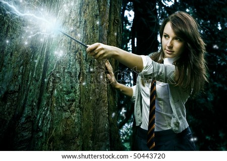 Teenage wizard girl with magic wand casting spells in a enchanted fantasy forest - stock photo