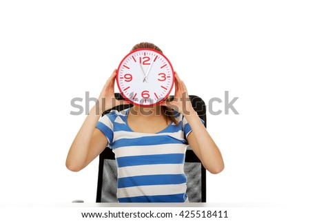 Teenage woman covering her face with a clock - stock photo
