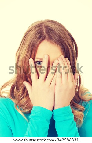 Teenage woman covering her face with hands  - stock photo